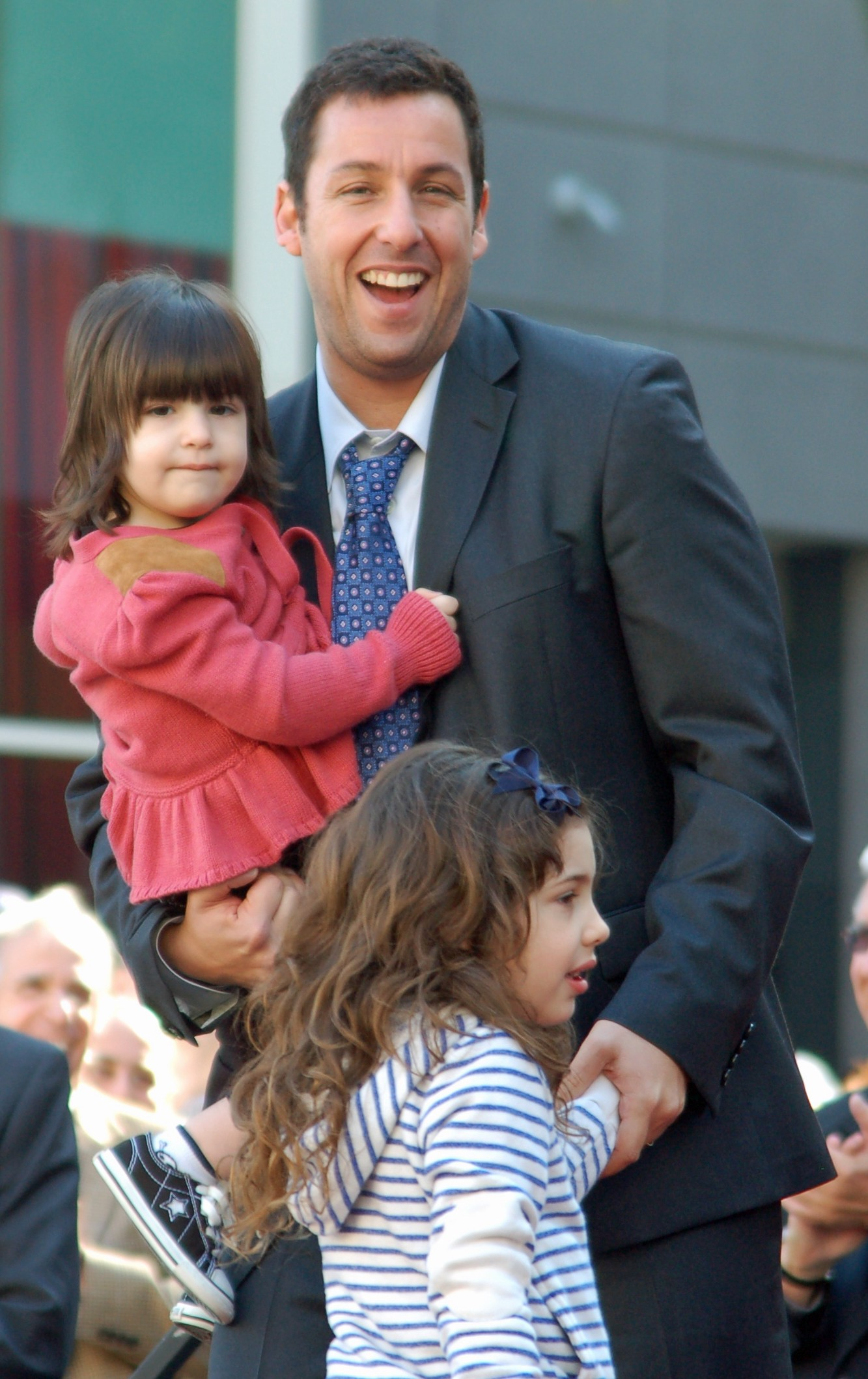 Adam Sandler is in a suit and tie, holding one of his daughters who has short brown hair and is wearing a pink top, his other daughter is standing in front of him she has longer curly hair and is in a blue and white striped top.