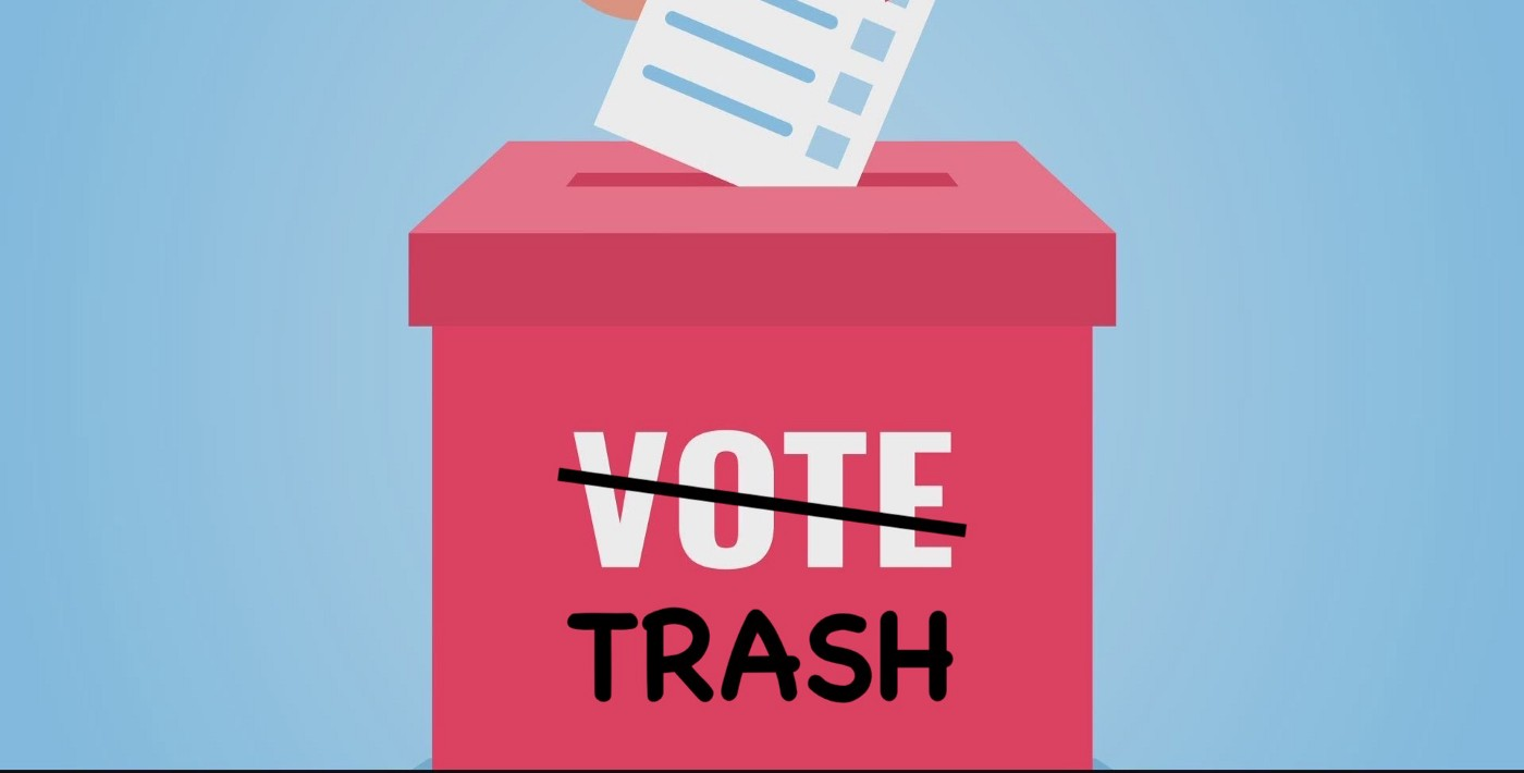 """A ballot being placed into a ballot box with the word """"VOTE"""" crossed out and replaced with the word """"TRASH""""."""