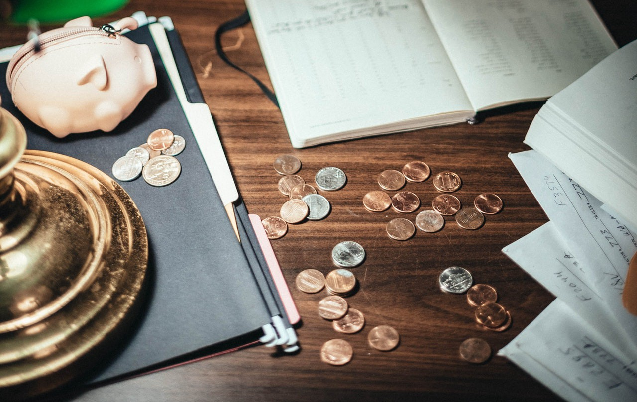 A wooden table with coins on it together with a open notebook and some papers. In the left corner is also a small pink piggy bank.