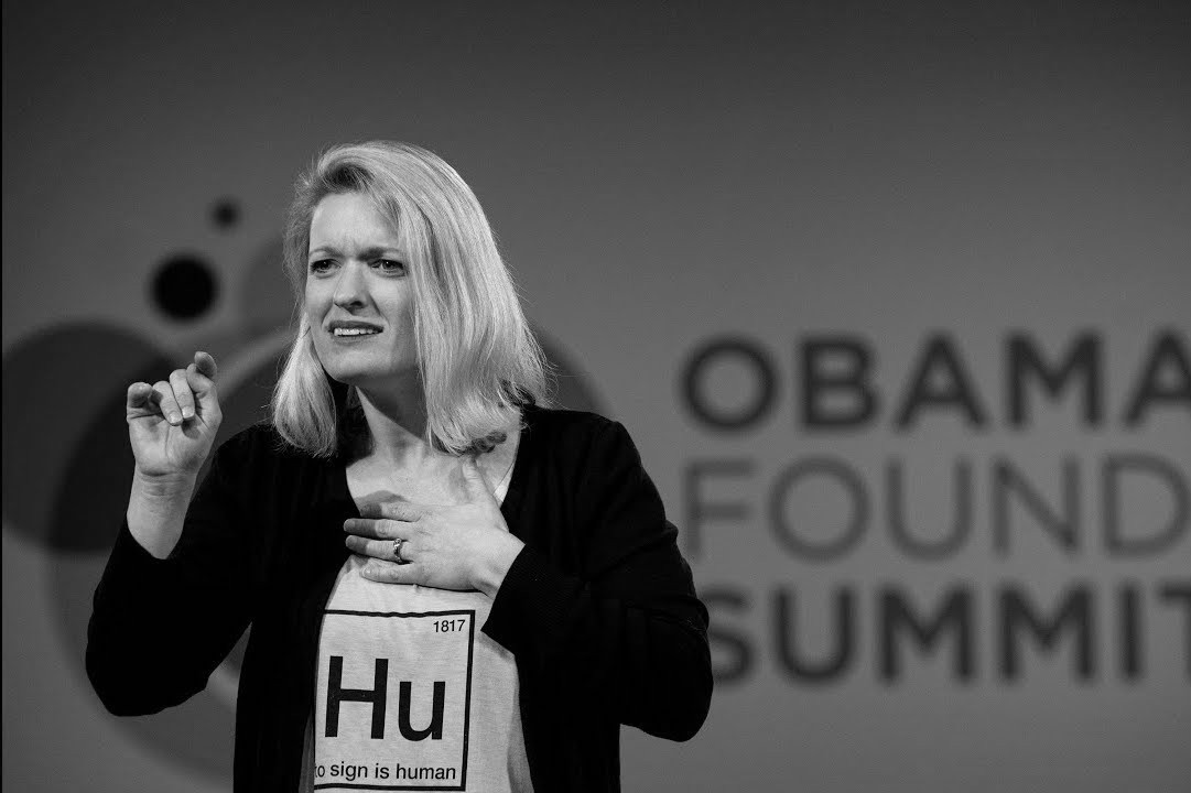 Melissa Malzkuhn presenting at the Obama Foundation Summit wearing a shirt that says, to sign is human.