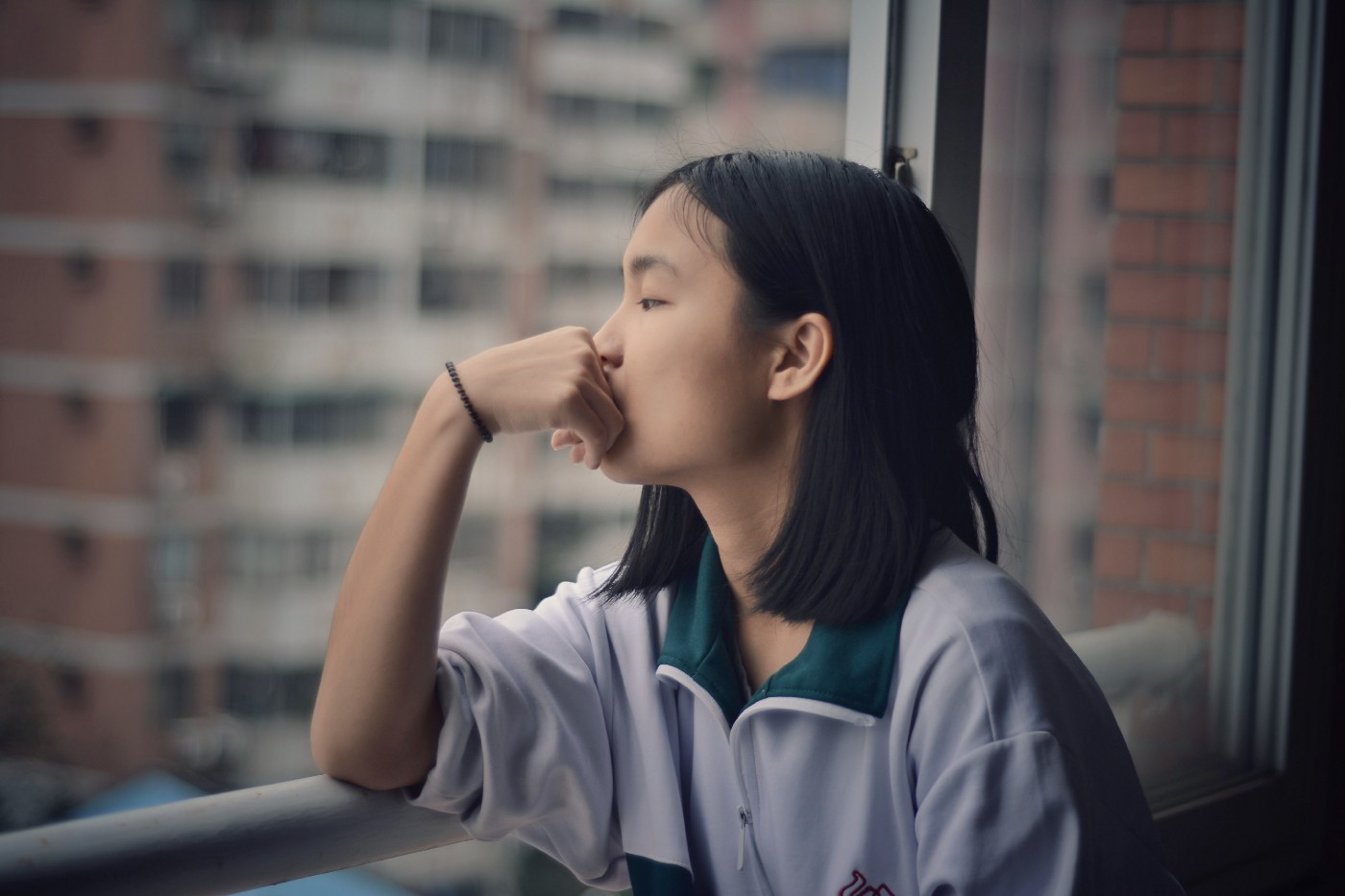 Young girl looking out of a window dreaming