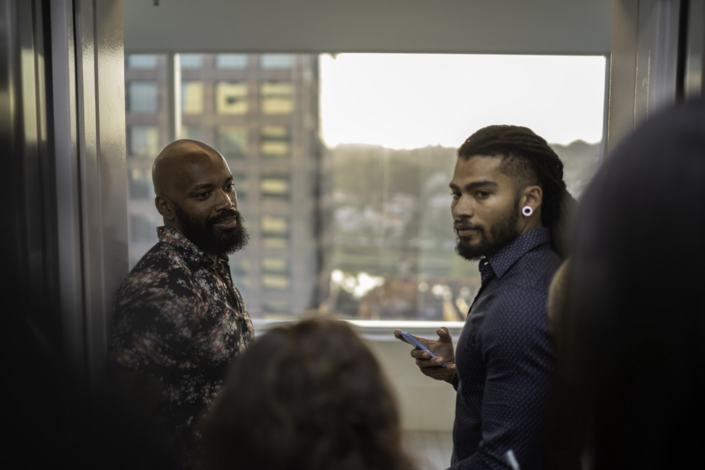 Two black men in front of an open elevator full of people.