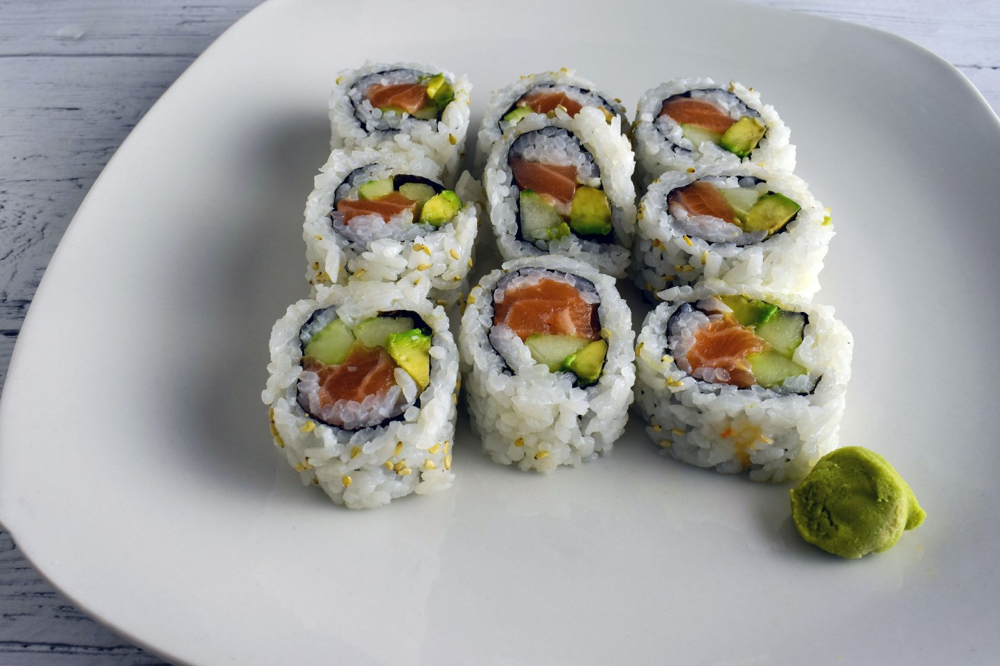 A plate holds several pieces of a California sushi roll.