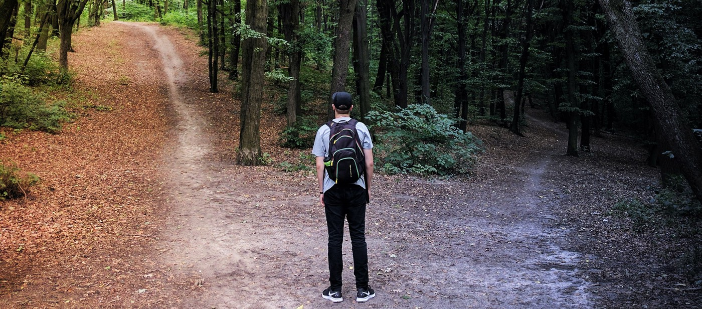 Young man with backpack standing at a crossroads in the middle of forest