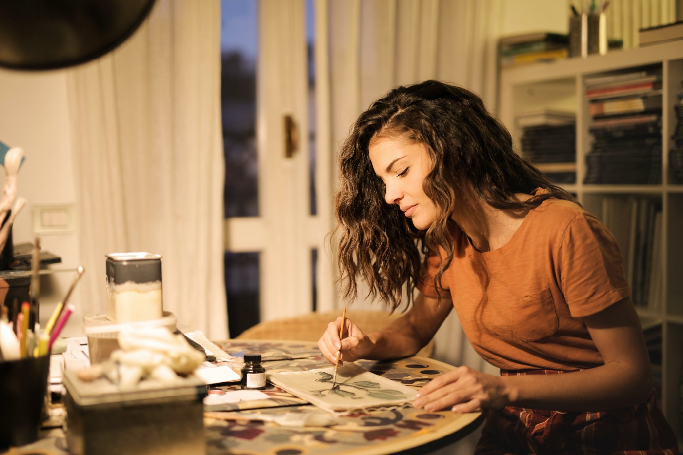 Woman is painting in an office space, likely in her apartment. The lighting is dim and homely.