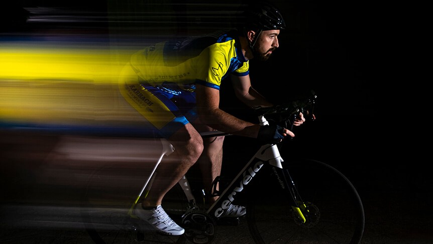 Road cyclist riding with slow sync motion blur behind him