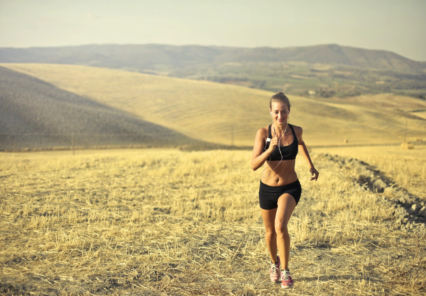 woman running in grassy fields on a sunny day