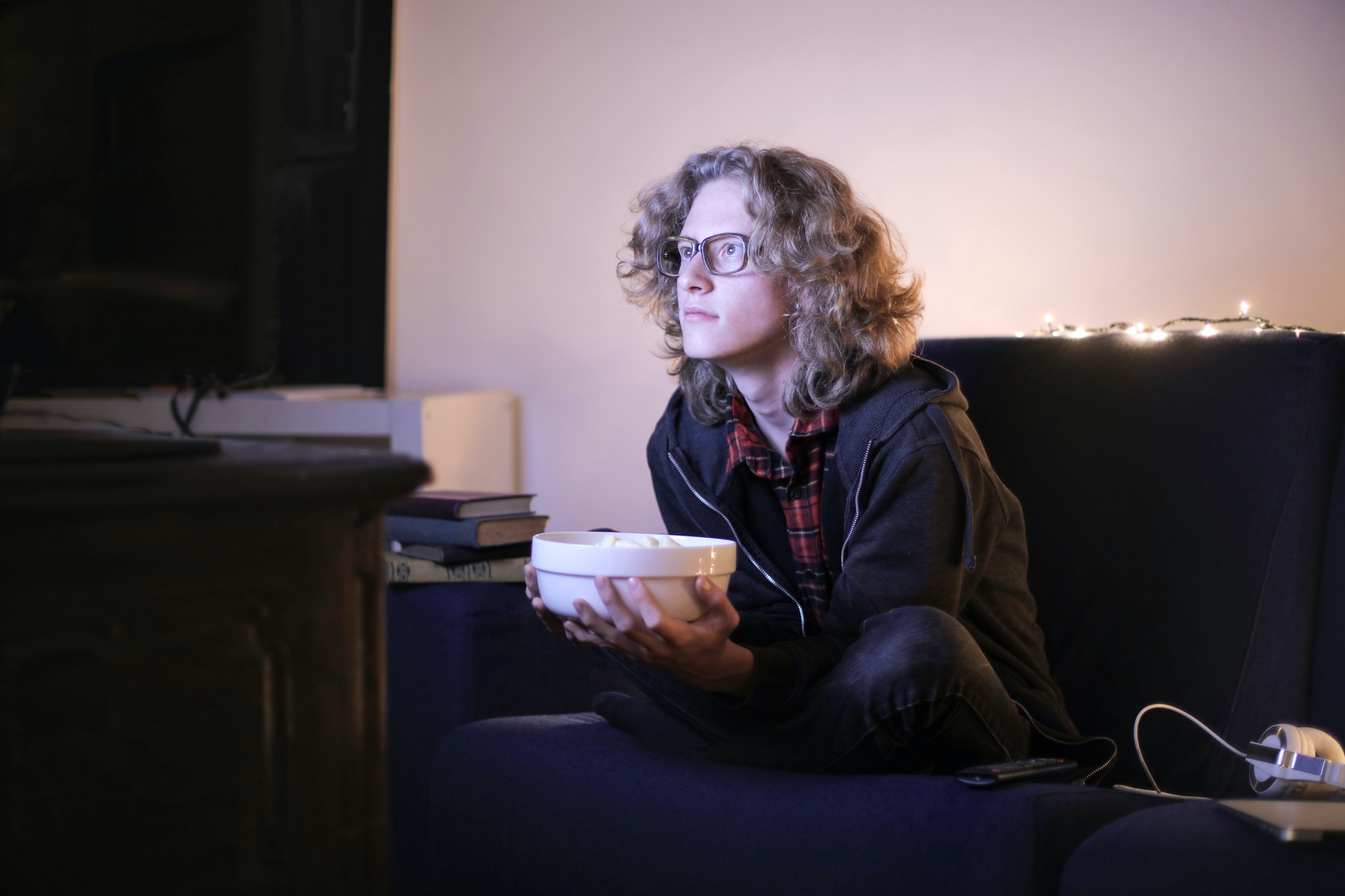 Person with light curly hair holding a popcorn bowl and illuminated by a TV screen they're staring intently into