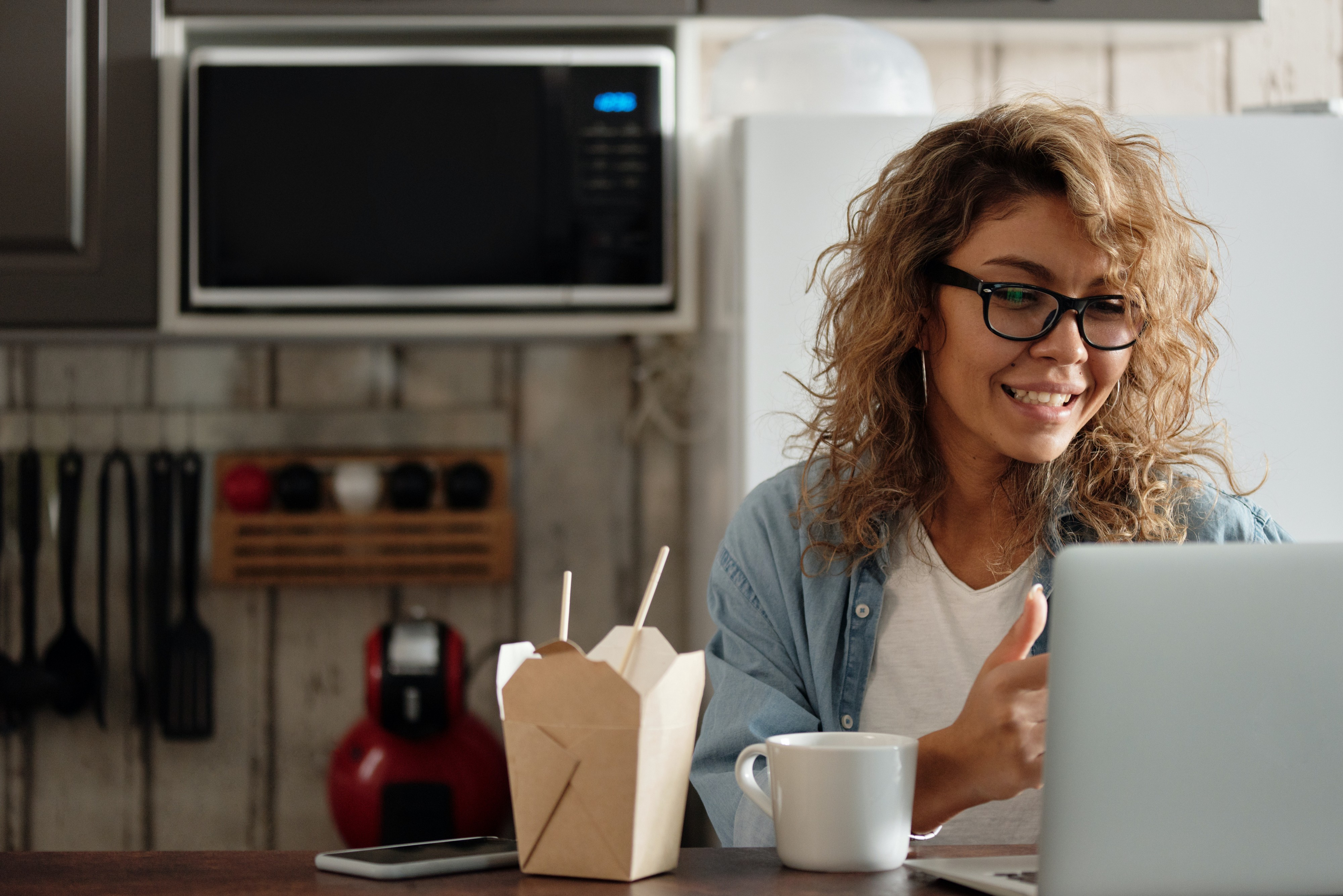 Woman using a laptop with takeout food and a cup of coffee.