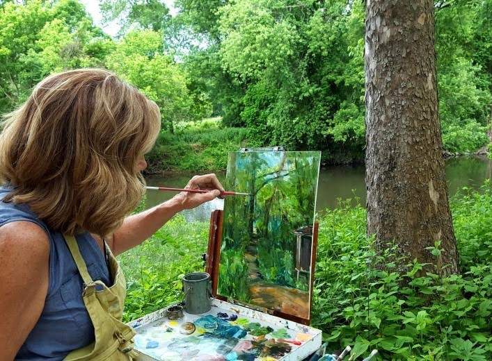 Woman painting a forest scene outdoors in a lush green setting by a creek.