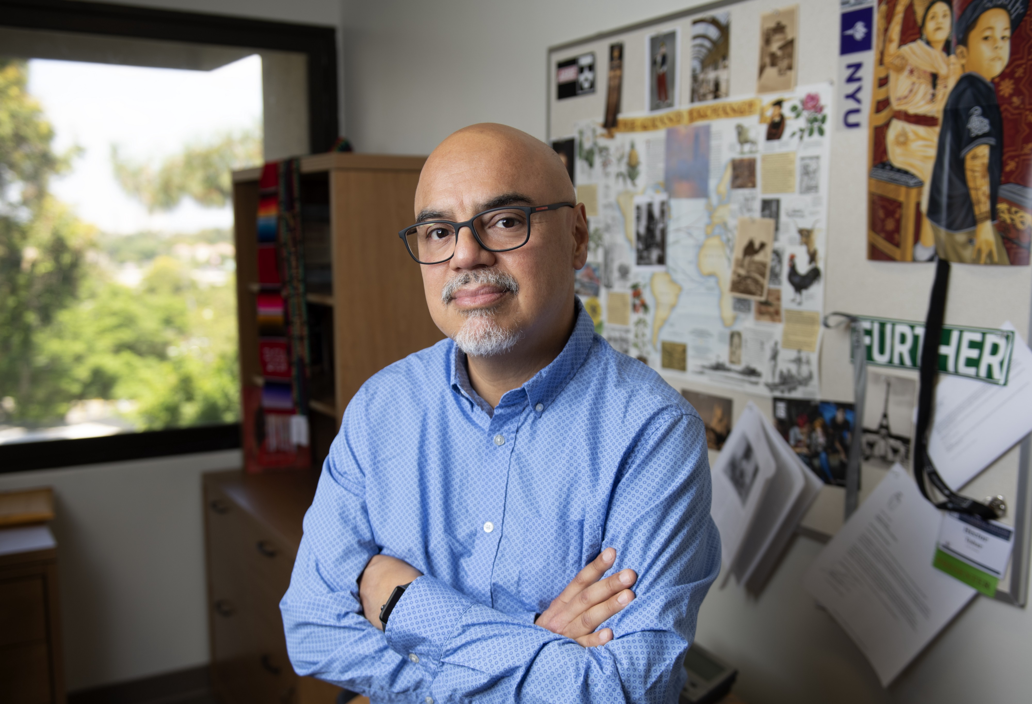 Héctor Tobar stands in his office with his arms crossed.