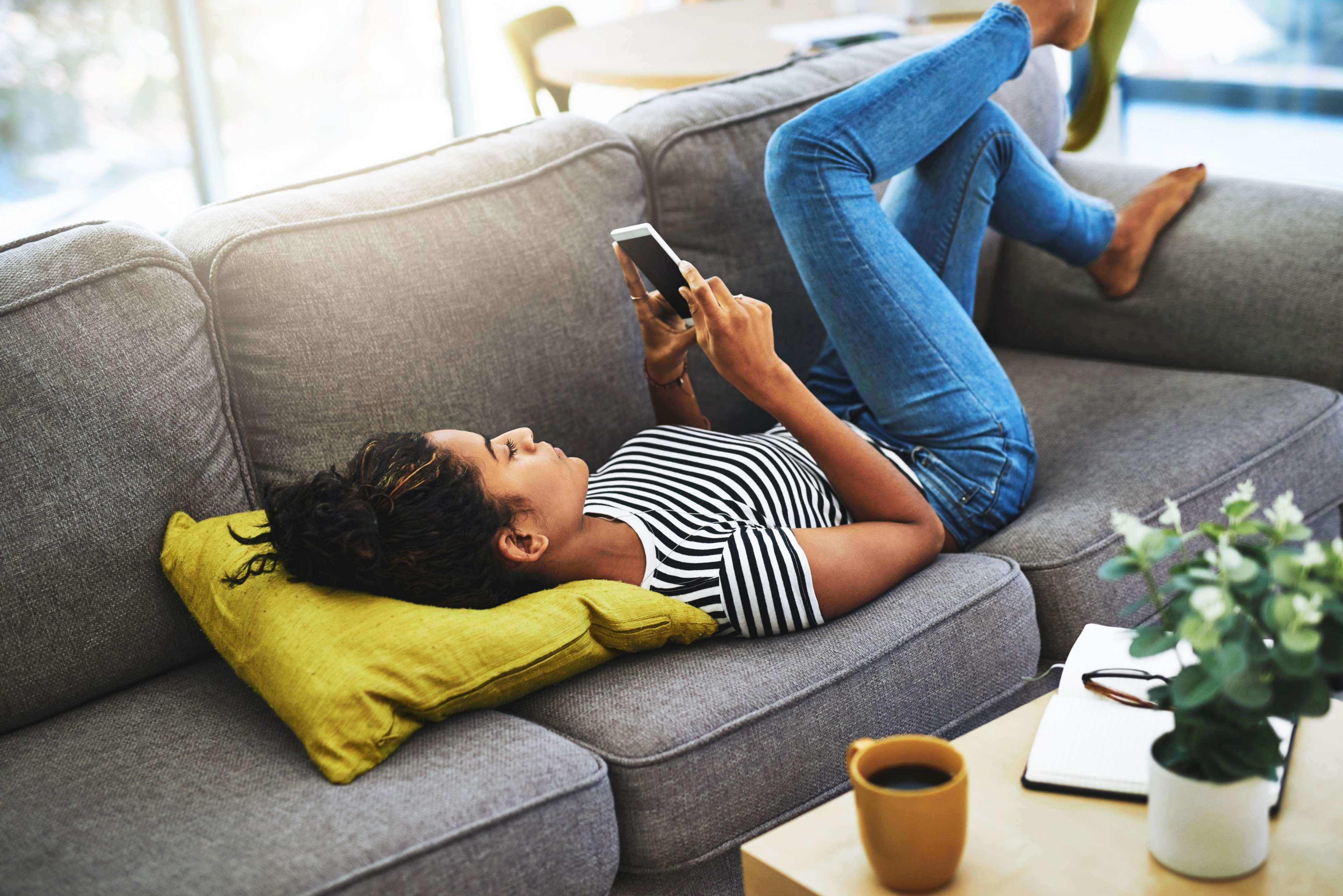 A woman scrolling down her phone while lying down on her couch.