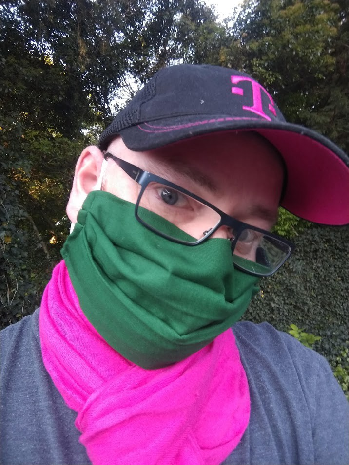 the author in a green face mask, pink scarf, and coordinating ballcap