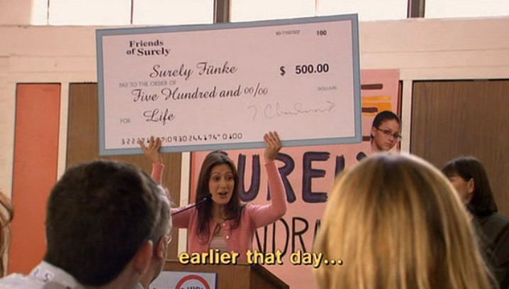 A representative from Friends of Surely holds up a giant check for five hundred dollars for Surely Fünke for life.