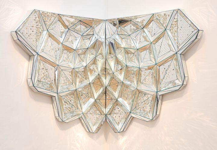 Sculptural artwork featuring faceted geometric glass arranged in a semicircular pattern.