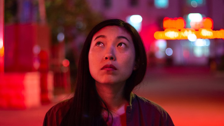 Awkwafina covered in red light, looking up