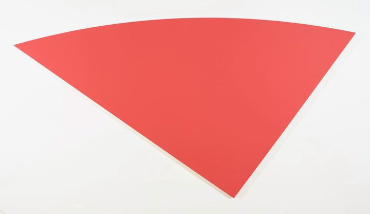 Curved triangular canvas painted entirely in a single hue of red.