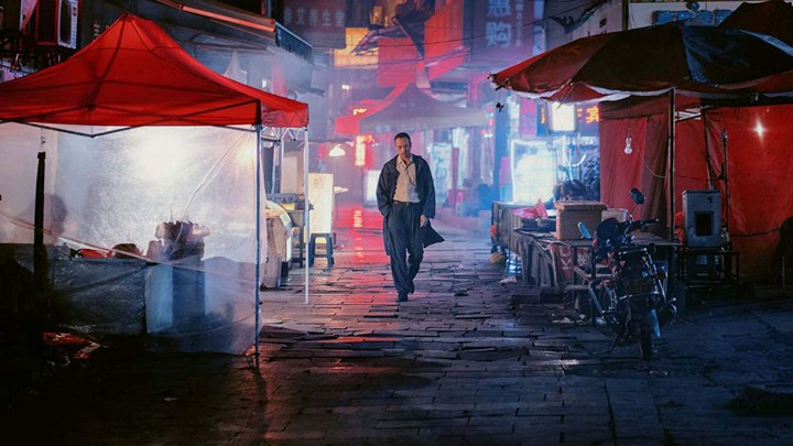 Huang Jue walking down a street, with bright red colours on the tents