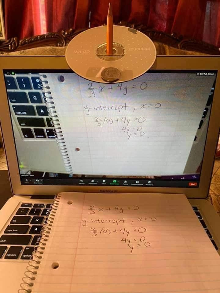A student using a compact disc as a mirror to project their keyboard over a zoom video call