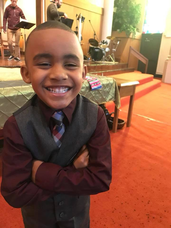Black boy in a suit vest, tie, and button up shirt five years old, arms crossed, smiling at camera.