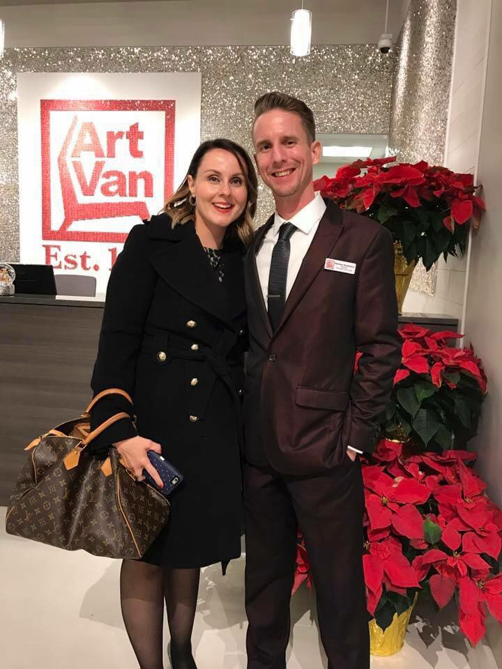 Matthew Bardeleben wearing shiny red suit and black velvet tie for Christmas party by red flowers with Whitney Bardeleben