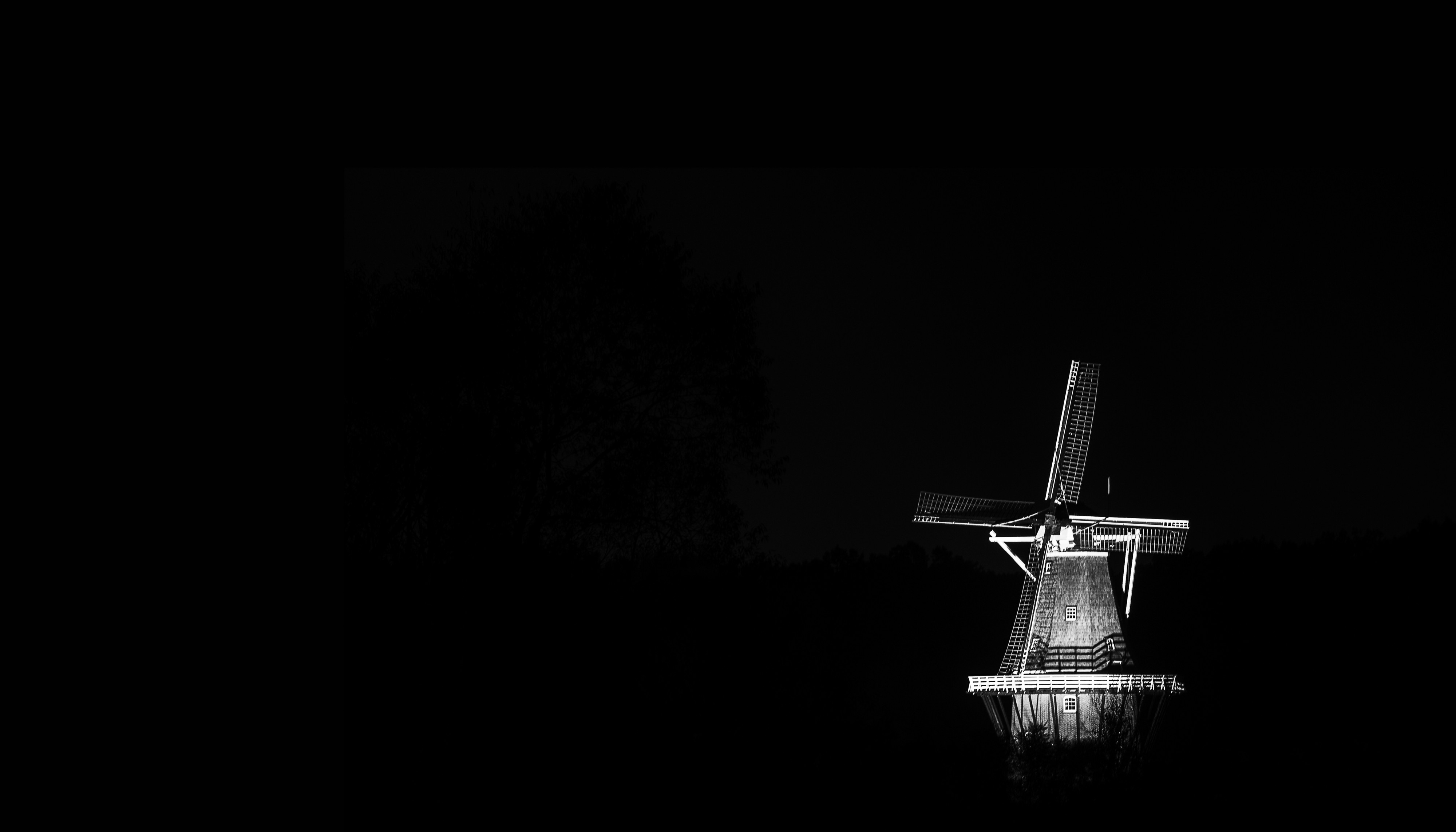 An old-fashioned windmill standing out starkly against a dark background.