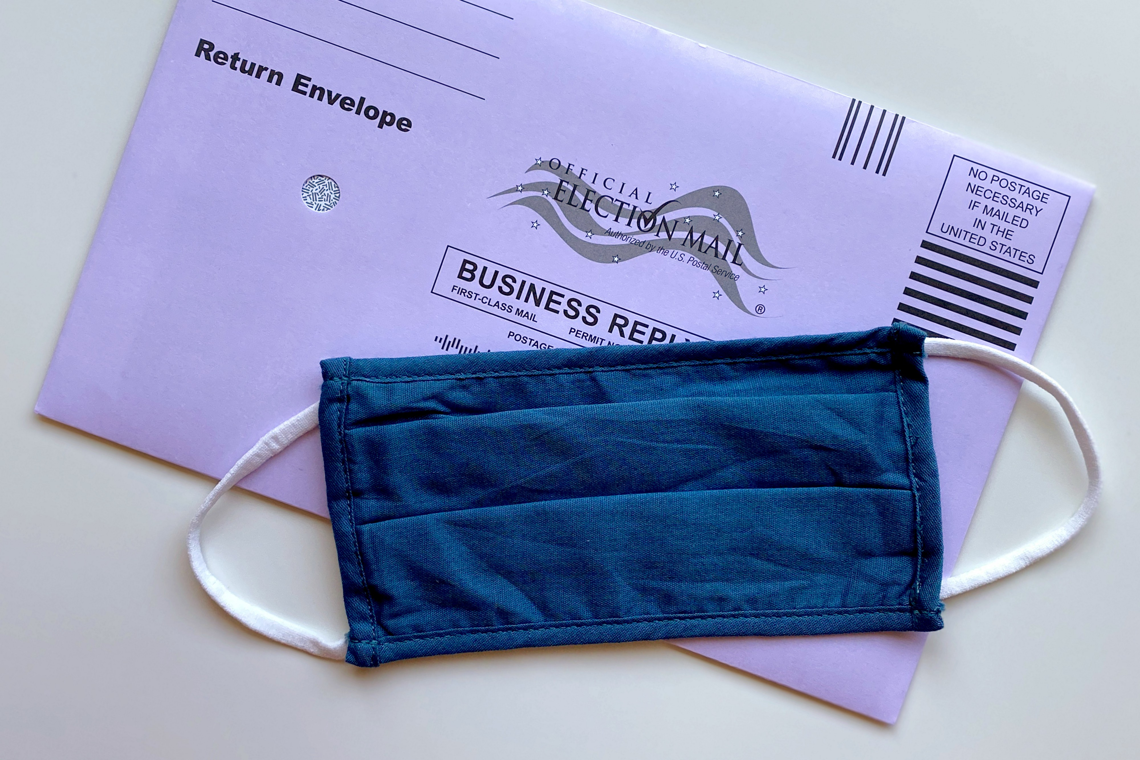 A postal vote envelope and a face mask