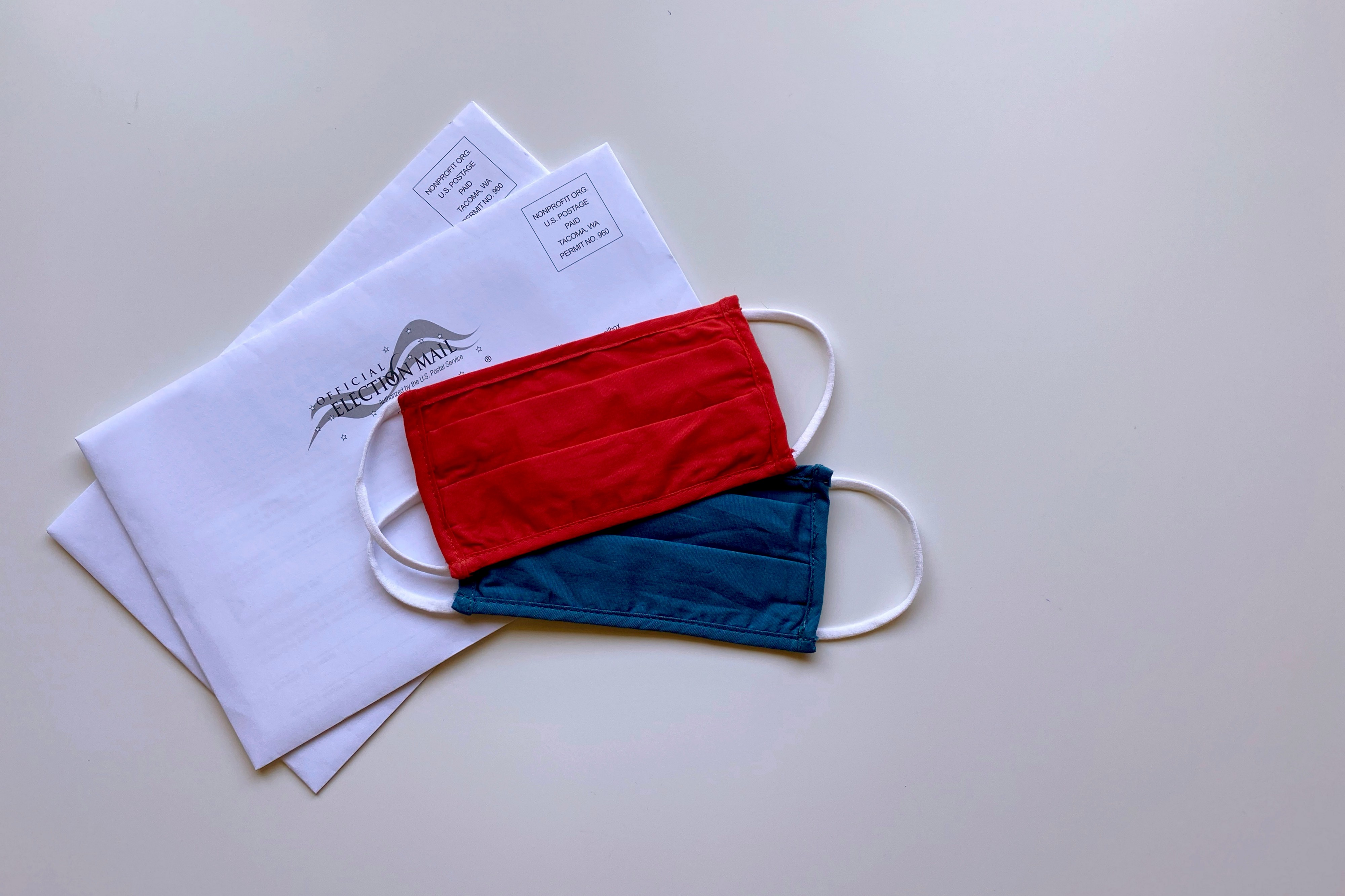 """Two """"Election Mail"""" envelopes stacked iwth a red mask and a blue mask laid on top"""