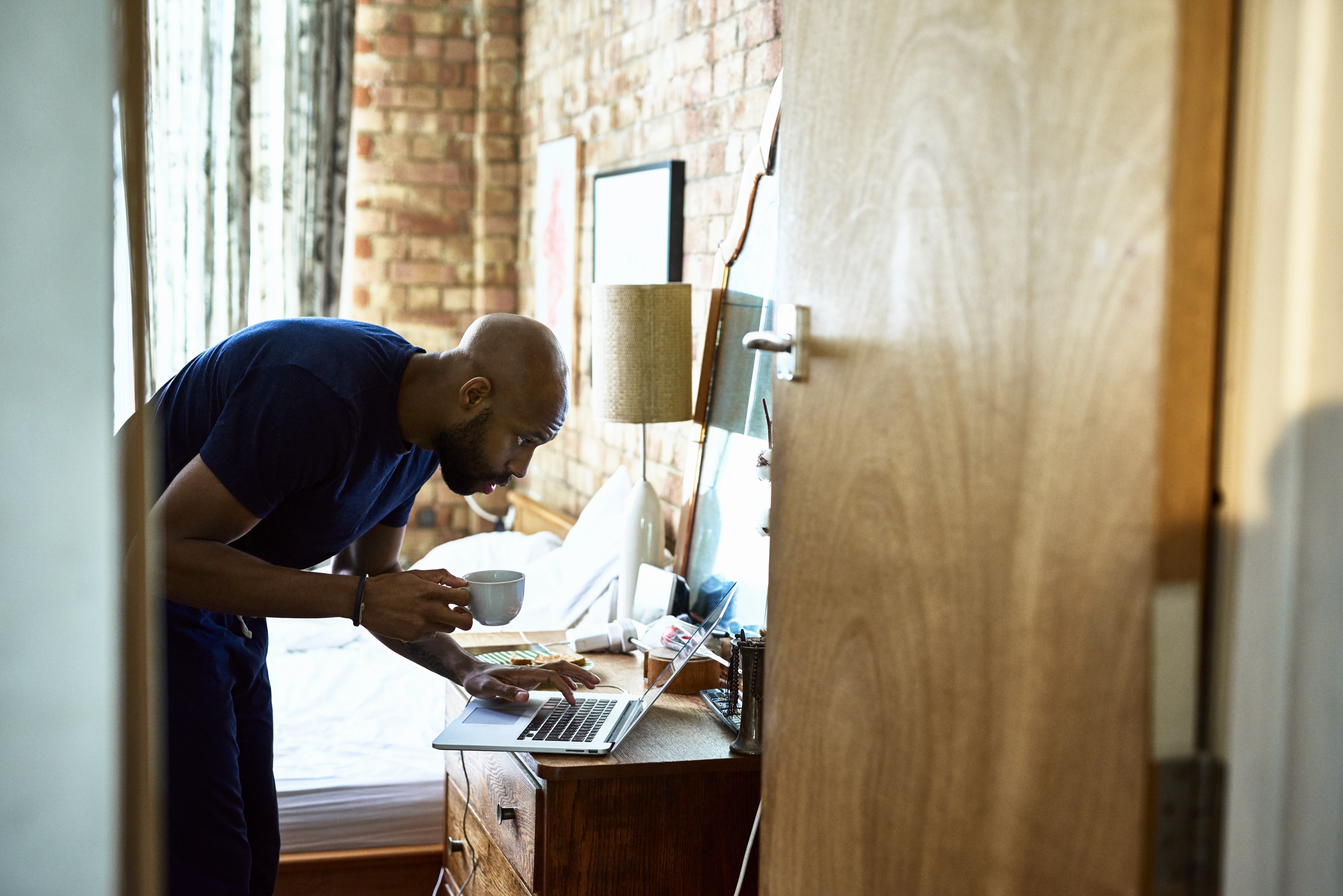 A man holds his coffee cup, checking emails on a laptop on his nightstand in his bedroom.