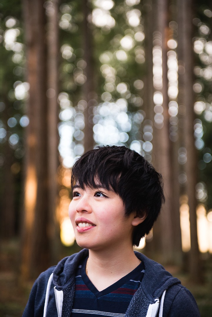 Photo of author: short black hair, brown eyes, stripey blue v neck shirt, blue hoodie, forest background.
