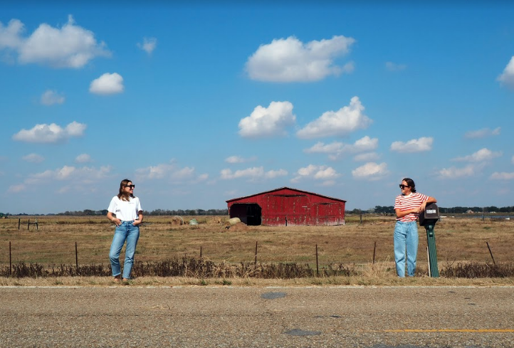 Two people standing about 15 feet apart on a country road, a red barn between them in the distance.