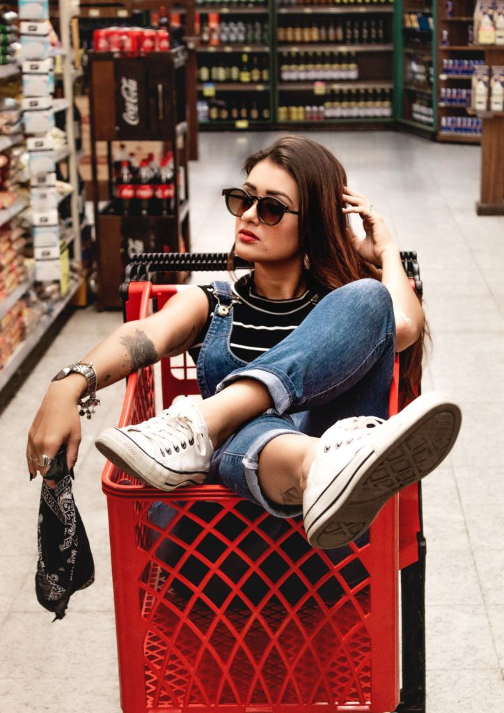A person wearing blue jeans sitting in a red shopping cart