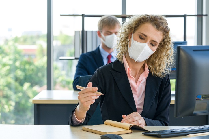 people working in an office with masks — social distancing