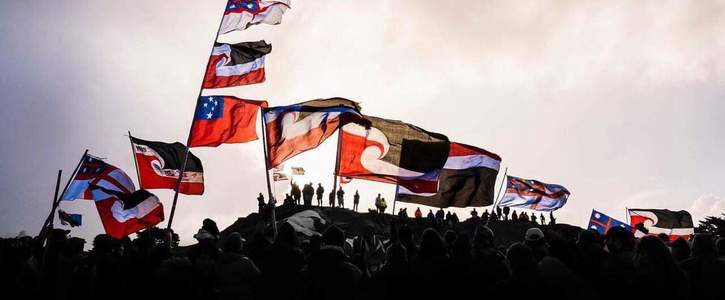 Tino rangatiratanga flags flying on a maunga (hill) with small human figures in silhouette underneath