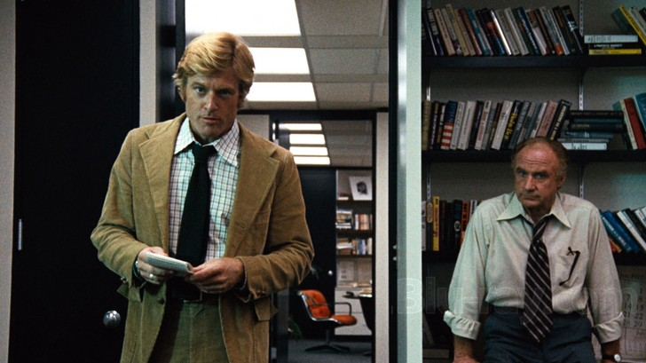 Still from the movie All the President's Men. Robert Redford bursting into an office with a man standing next to him.