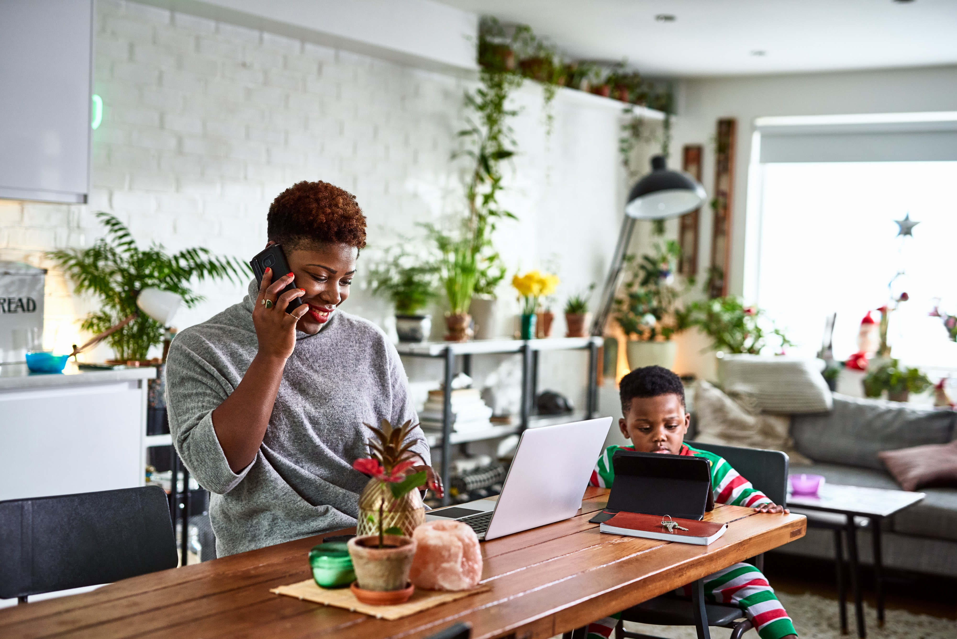 An adult woman on the phone looking at her laptop on the dining table while her son uses a digital tablet.