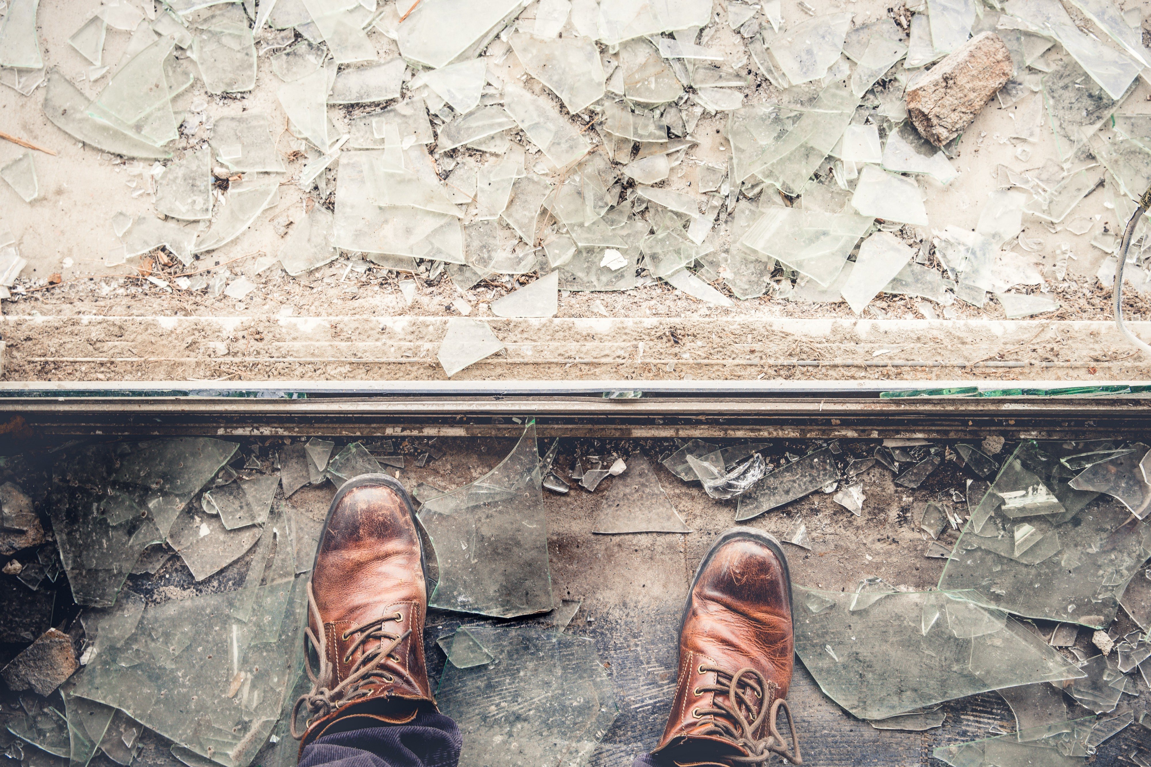 A pair of brown work boots stand amidst a sea of broken glass