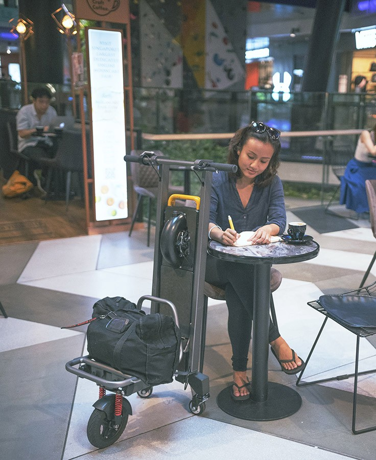 woman with cargo e-scooter in a cafe at a mall