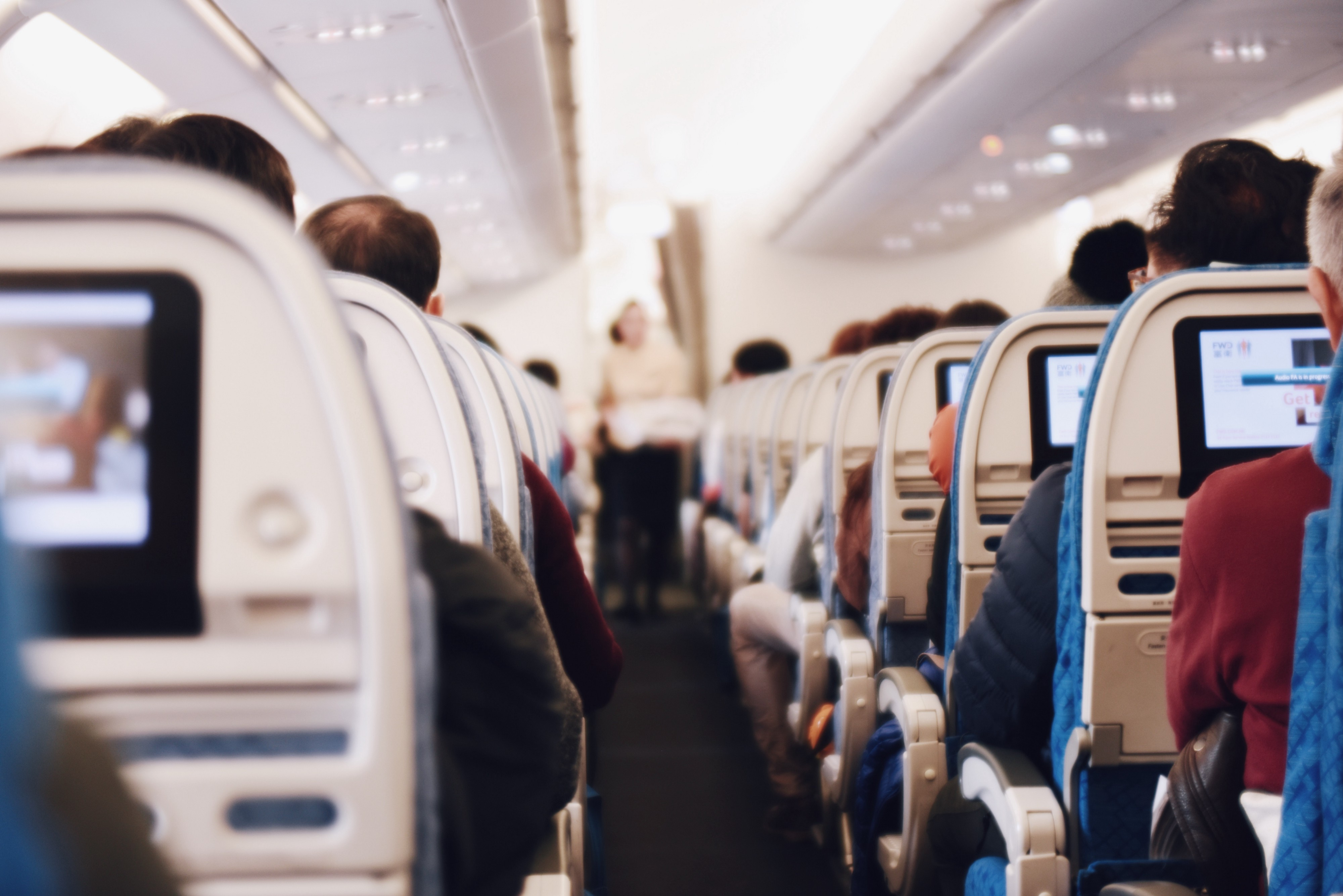 Photo of inside an airplane, looking down the aisle at the backs of passengers in seats. by Suhyeon Choi.