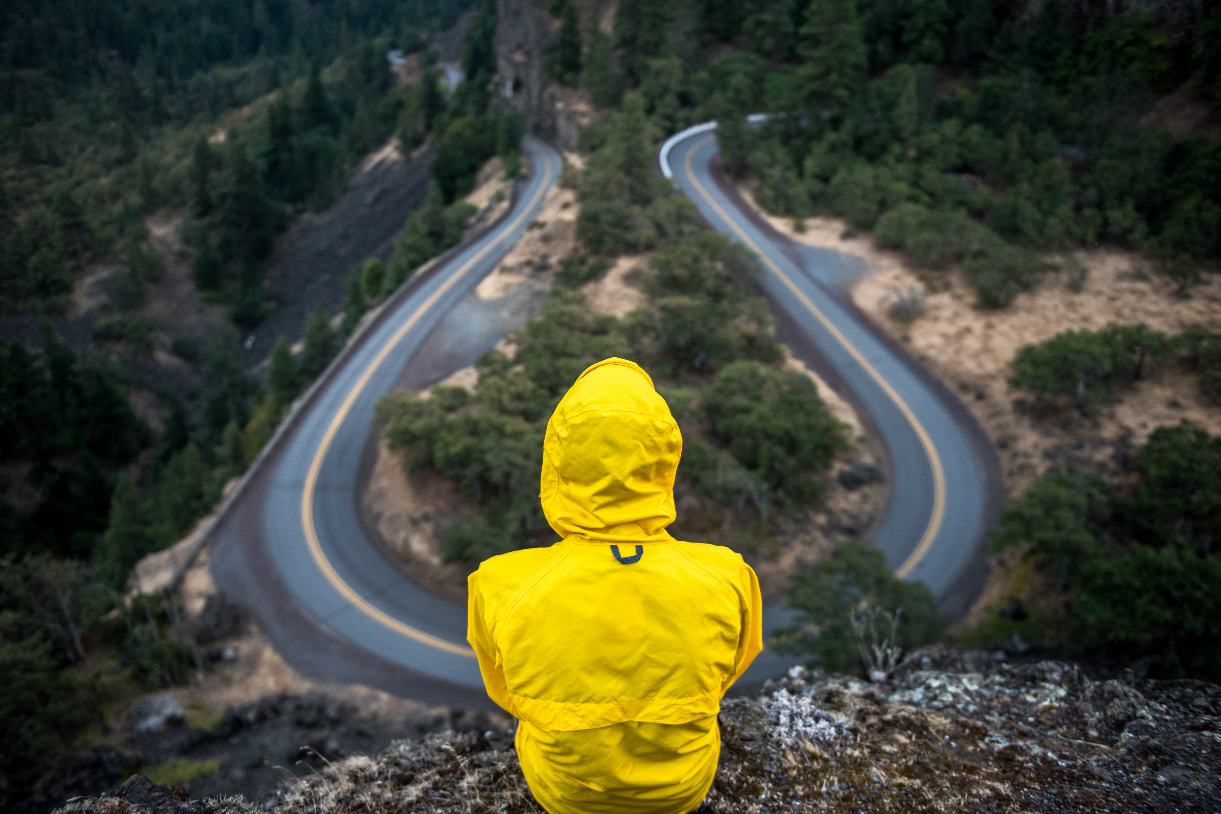A person in a yellow rain jacket overlooks a fork in the road from on top of a hill.