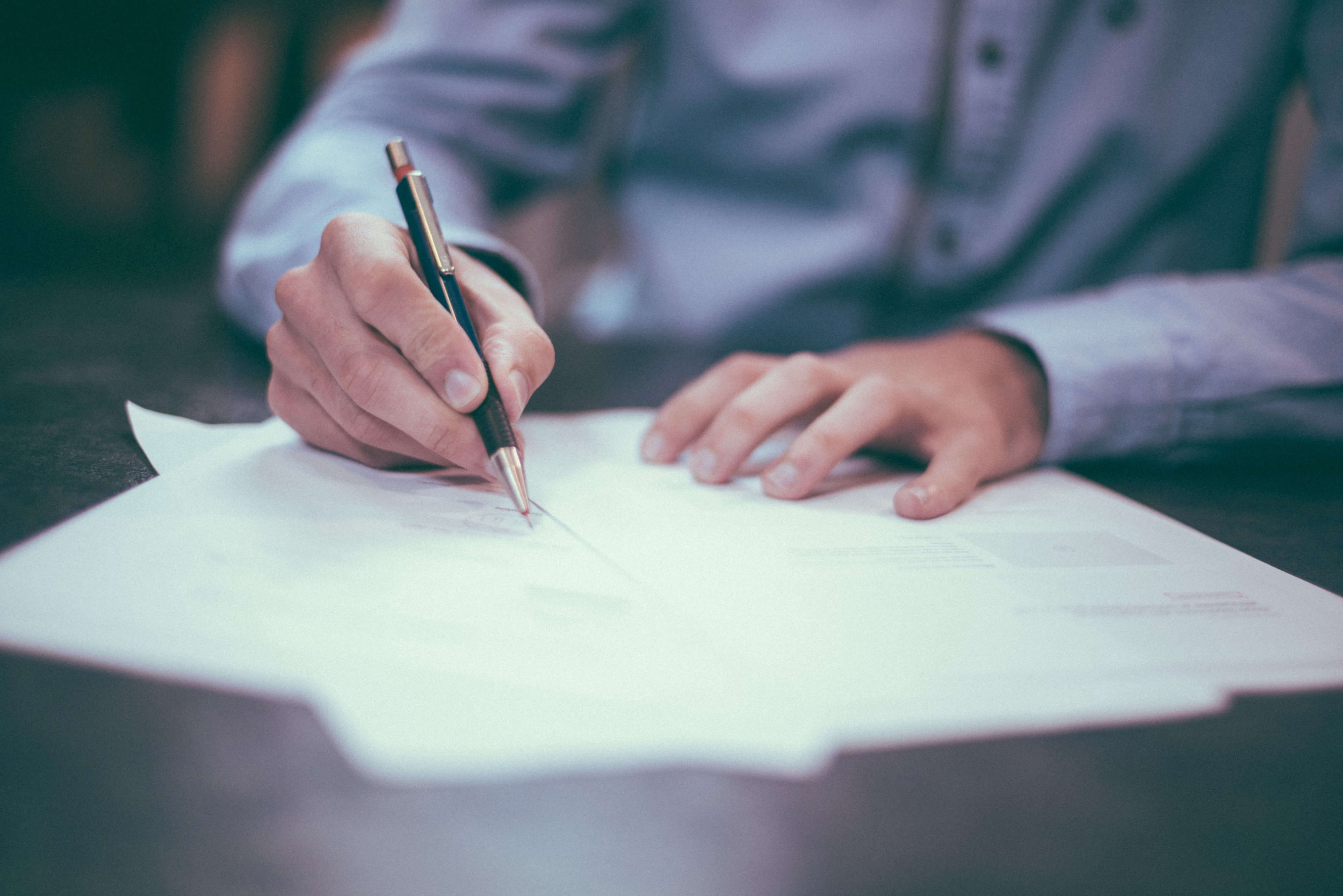 A person with a blue button up shirt holding a pen writing on paper