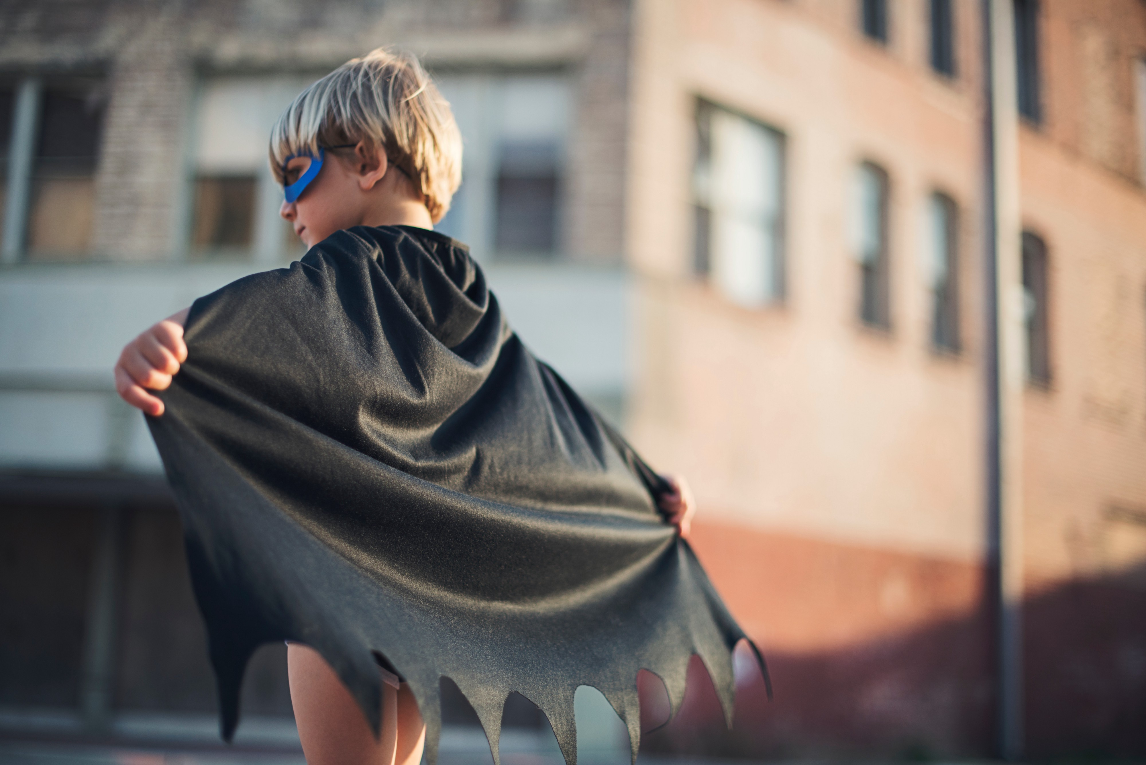 Image of a little boy wearing a mask and super hero cape