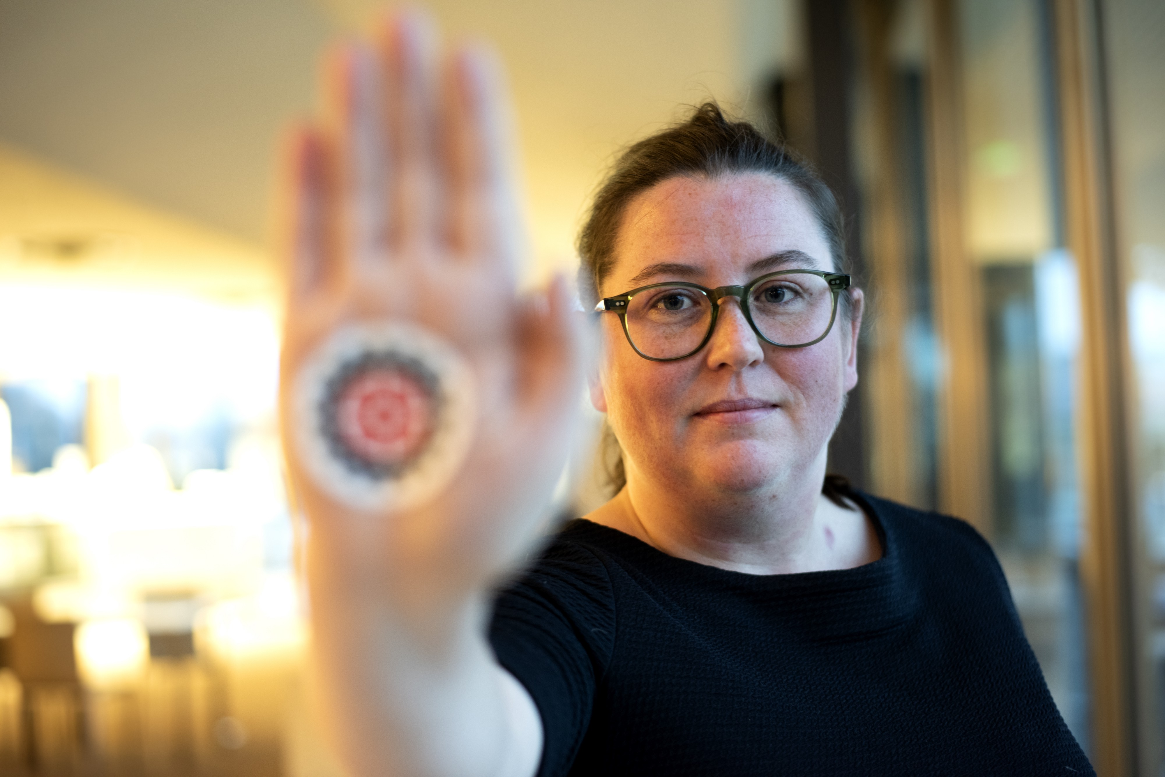 Laura Nolan looks, with her hand outstretched looks into the camera with the Campaign to Stop Killer Robots logo on her hand