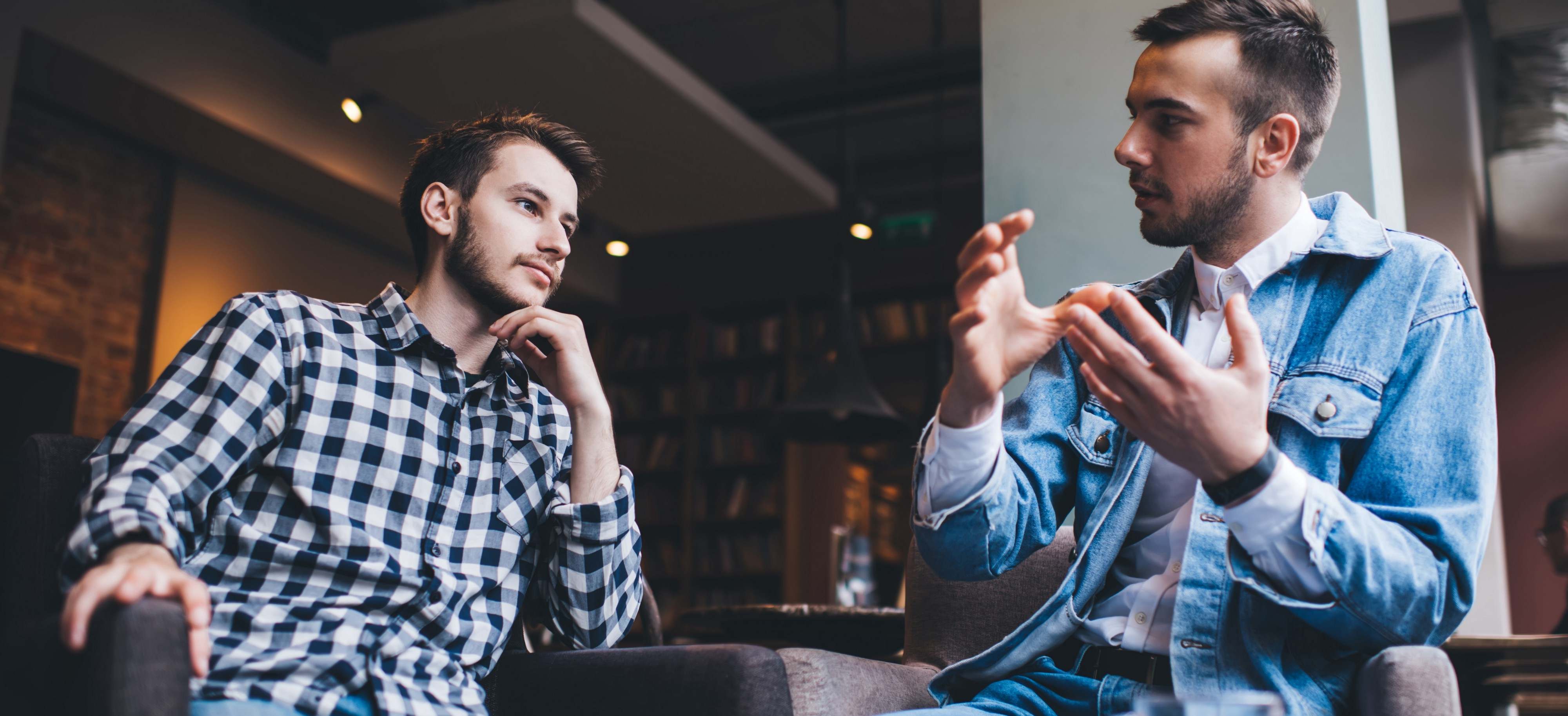 Photo of two men engaging in a discussion. Photo Credit: Adobe Stock Images.