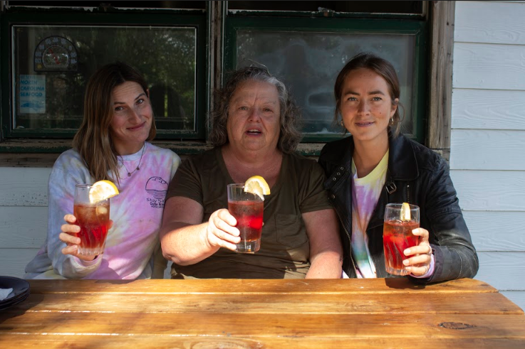A grandma sitting in between two young women. They're all holding up glasses of red liquid with lemon wedges on the rims.
