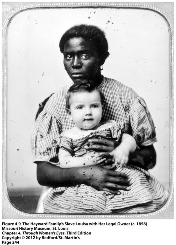 Black and white photograph of black woman wearing a long checkerd dress holding a white child from 1858.
