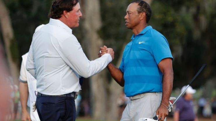 In this May 10, 2018, file photo, Phil Mickelson, left, and Tiger Woods shake hands after the first round of the Players Championship golf tournament, in Ponte Vedra Beach, Fla.