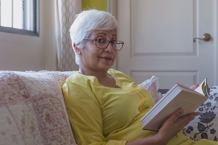 elegant middle aged woman looking into camera while holding novel