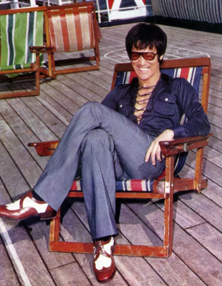 """Dapper """"Fist of Fury"""" star Bruce Lee reclines in April 1972 aboard the MS Coral Princess cruise liner in Hong Kong"""