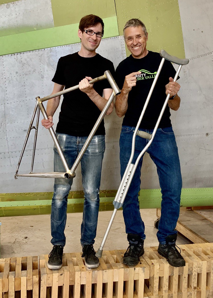 One man holding a bicycle frame and another man holding a crutch